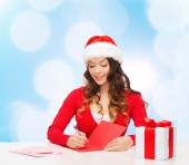 Smiling woman with gift box writing letter — Stock Photo
