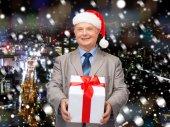 Sonriente hombre en traje y papá noel ayudante sombrero con regalo — Foto de Stock