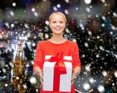 Smiling woman in red clothes with gift box — Stock Photo