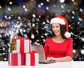 Smiling woman in santa hat with gifts and laptop — Stock Photo
