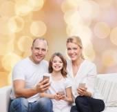 Happy family with smartphones — Stock Photo