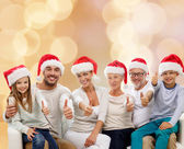 Happy family in santa hats showing thumbs up — Stock Photo