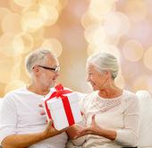Feliz pareja senior con caja de regalo en casa — Foto de Stock