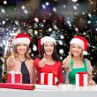 Smiling women in santa helper hats packing gifts — Stock Photo #57527297