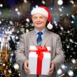 Smiling man in suit and santa helper hat with gift — Stock Photo #57527305