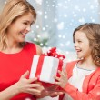 Smiling mother and daughter with gift box at home — Stock Photo #57552155