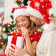 Smiling father and daughter holding gift box — Stock Photo #57552713