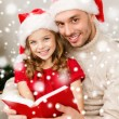 Smiling father and girl in santa hats reading book — Stock Photo #57552727