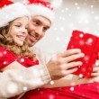 Smiling father and girl in santa hats reading book — Stock Photo #57552739