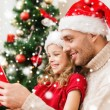 Smiling father and girl in santa hats reading book — Stock Photo #57552757