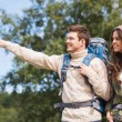 Smiling hikers with backpacks pointing finger — Stock Photo #57555927