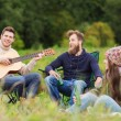 Group of tourists playing guitar in camping — Stock Photo #57556345