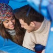 Smiling couple of tourists looking out from tent — Stock Photo #57556475