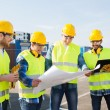 Group of builders with tablet pc and blueprint — Stock Photo #57556707