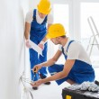 Builders with tablet pc and equipment indoors — Stock Photo #57557113