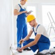 Builders with tablet pc and equipment indoors — Stock Photo #57557135