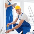 Builders with tablet pc and equipment indoors — Stock Photo #57557155