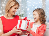 Smiling mother and daughter with gift box at home — Stock Photo