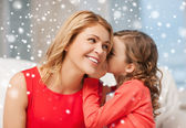 Happy mother and girl whispering into ear — Stock Photo