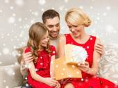 Smiling family holding gift box — Стоковое фото