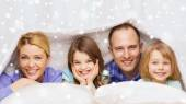 Happy family with two kids under blanket at home — Stock fotografie