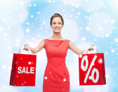 Young woman in red dress with shopping bags — Stock Photo