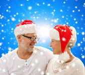 Happy senior couple in santa helper hats — Stock Photo