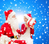Smiling little girl with santa claus and gifts — Stok fotoğraf
