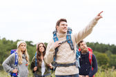 Smiling hikers with backpacks pointing finger — Stock Photo