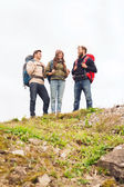 Group of smiling friends with backpacks hiking — Foto de Stock