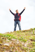 Tourist with beard and backpack raising hands — Stock Photo
