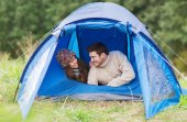 Smiling couple of tourists looking out from tent — Stock Photo
