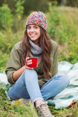Smiling young woman with cup sitting in camping — ストック写真