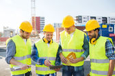 Group of smiling builders with tablet pc outdoors — Stock Photo