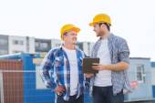 Smiling builders in hardhats with tablet pc — Stock Photo