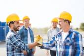 Group of smiling builders shaking hands outdoors — Stock Photo