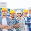 Group of smiling builders in hardhats outdoors — Stock Photo #57720167