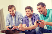Smiling friends playing video games at home — Stock fotografie