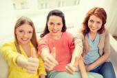 Three girlfriends showing thumbs up at home — Stock Photo