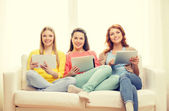 Three smiling teenage girls with tablet pc at home — Stock Photo