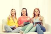 Три улыбаясь девочек-подростков с планшетного Пк на дому — Стоковое фото