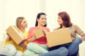 Smiling teenage girls with cardboard boxes at home — Stock fotografie
