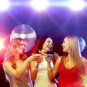 Drei lächelnde frauen mit cocktails und disco-kugel — Stockfoto