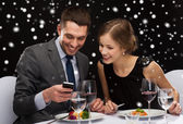 Smiling couple with smartphone at restaurant — Stockfoto