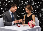 Smiling couple with red gift box at restaurant — ストック写真