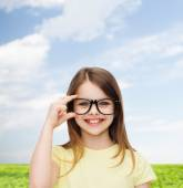 Smiling cute little girl in black eyeglasses — Stock fotografie
