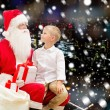 Smiling little boy with santa claus and gifts — Stock Photo #57772061