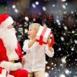 Smiling little boy with santa claus and gifts — Stock Photo #57772101