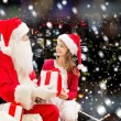 Smiling little girl with santa claus and gifts — Stock Photo #57772123