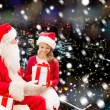 Smiling little girl with santa claus and gifts — Stock Photo #57772139